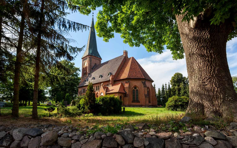 Die neugotische einschiffige Kirche mit dem quadrischen Turm mit einem spitzen Turmhelm thront oberhalb einer Steinmauer.