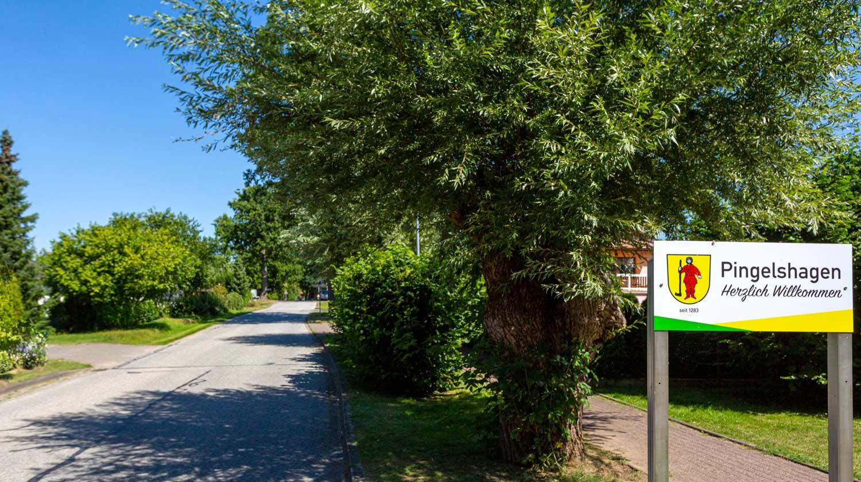 Herzlich Willkommen in Pingelshagen steht auf dem Gemeindeschild direkt an der grün gesämten Strasse.