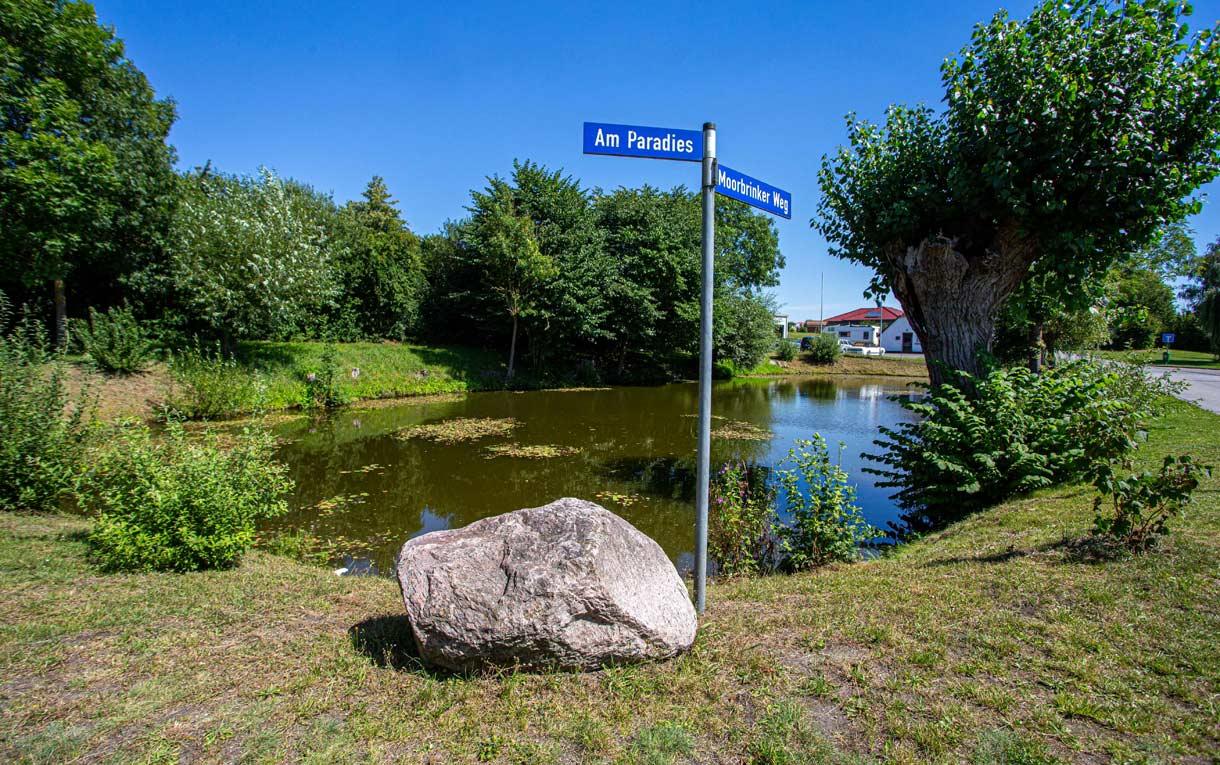 In Pingelshagen liegt der Dorfteich zwischen dem Paradies und dem Moorbrinker Weg, wie die zwei Strassenschilder am Ufer zeigen.