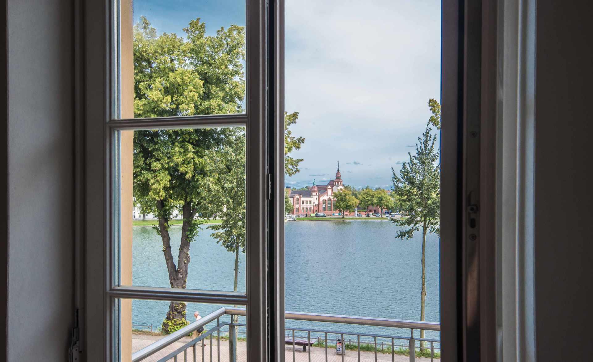 Durch das offenen Fenster fällt der Blick über den Pfaffenteich in Schwerin auf das E-Werk